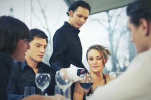 Empregado de mesa a servir vinho