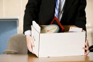 Homem carrega os seus pertences após layoff