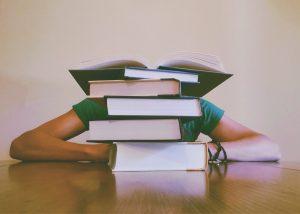 pessoa escondida atrás de livros em casa
