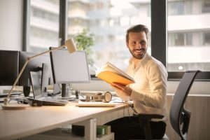 homem a trabalhar ao computador com livro