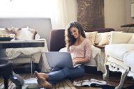 mulher contente em casa a trabalhar ao computador