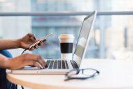 mulher a usar computador e telemovel para comunicar