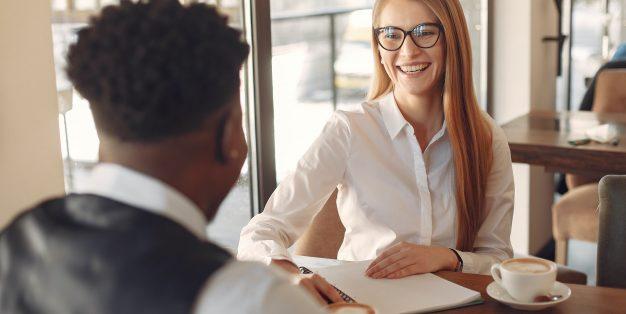 mulher a sorrir para homem em entrevista