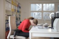 mulher sentada à secretária do trabalho com a cabeça em baixo
