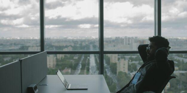 homem no trabalho com computador e postura reclinada