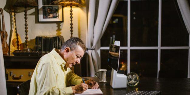 homem a trabalhar ao computador na mesa da sala