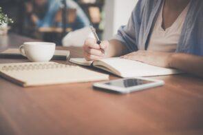 mulher a escrever em caderno