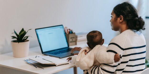 mulher em casa a trabalhar com filho no colo